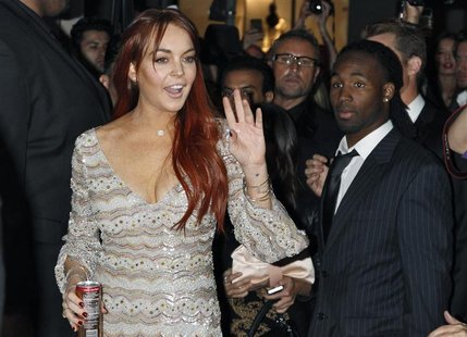Actress Lindsay Lohan waves as she arrives for the Mr. Pink Ginseng Drink launch party at the Beverly Wilshire Hotel in Beverly Hills, Calif