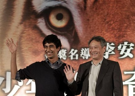 "Taiwan-born director Ang Lee (R) and cast member Suraj Sharma of India wave during a news conference to promote their latest film ""The Life"