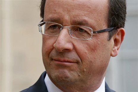 France's President Francois Hollande listens as a guest speaks in the courtyard following a meeting at the Elysee Palace in Paris, November