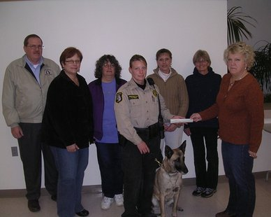 "Allegan Co. Sheriff's Deputy Kim Thornington, with ""Lucky"" the dog to her left, receives a $3,000 check from Kim Caines of the Holland Kennel Club in a ceremony at the Howard Miller Center in Zeeland. (photo courtesy Allegan Co. Sheriff's Dept.)"