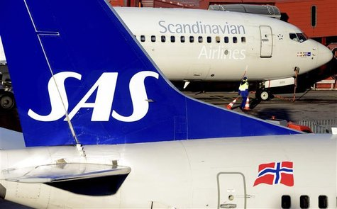 A ground staffer carries warning cones between two SAS Boeing 737 aircrafts parked at Arlanda airport's Terminal Five, north of Stockholm No