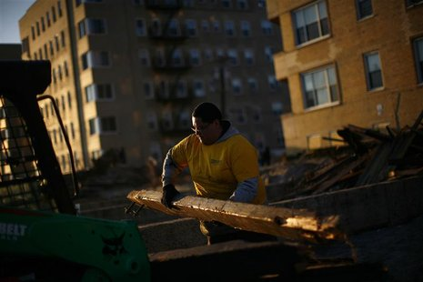 A worker removes debris from the destroyed boardwalk in the Rockaways section of the Queens borough of New York November 17, 2012. REUTERS/E