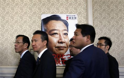 Members of the ruling Democratic Party of Japan stand next to a poster of Japanese Prime Minister Yoshihiko Noda after a meeting at the parl