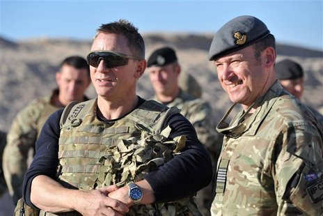Actor Daniel Craig (L) speaks to military personnel during a visit to Camp Bastion in Helmand Province, Afghanistan November 18, 2012. Craig