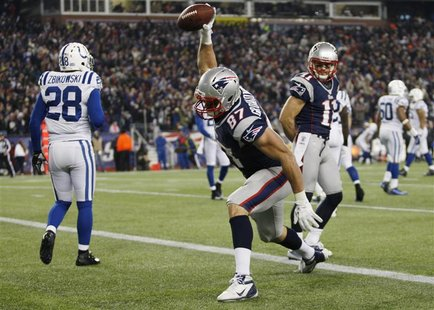 New England Patriots tight end Rob Gronkowski (C) celebrates his touchdown against the Indianapolis Colts as Colts safety Tom Zbikowski (L)