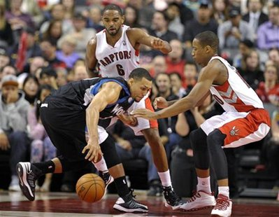 Minnesota Timberwolves guard Brandon Roy (L) grabs a loose ball in front of Toronto Raptors defenders Alan Anderson and DeMar DeRozan (R) du