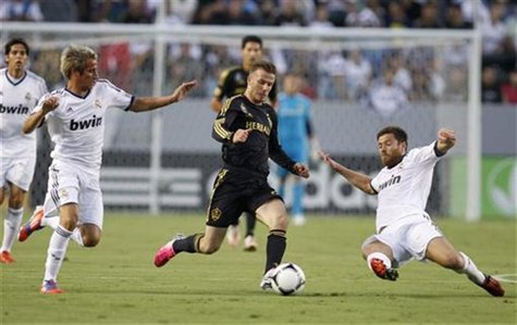 Los Angeles Galaxy's David Beckham (C) chases the ball between Real Madrid's Fabio Coentrao (L) and Xabi Alonso (R) during the first half of