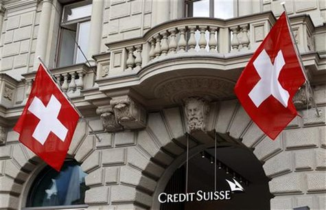 Switzerland national flags fly beside the logo of Swiss bank Credit Suisse (CS) at the company's headquarters in Zurich April 13, 2012. REUT