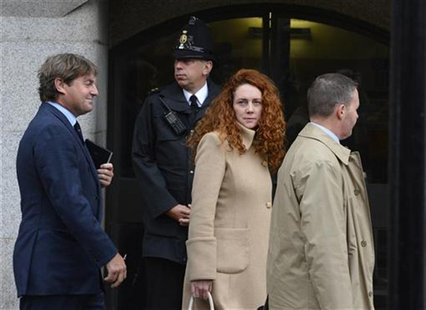 Former News International chief executive Rebekah Brooks and her husband Charlie (L) leave the Old Bailey court in London September 26, 2012