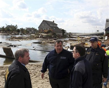 Governor Chris Christie (2nd L) surveys the Hurricane Sandy damaged areas along Rt 35 in Bayhead, New Jersey, November 2, 2012 in this hando