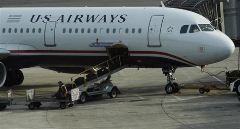A worker is seen loading luggage on a plane from US Airways at Newark Liberty International Airport in Newark, New Jersey November 15, 2012.