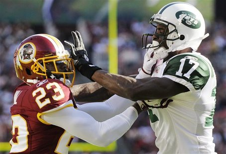 Washington Redskins cornerback DeAngelo Hall (L) and receiver Plaxico Burress continue to go at each other after the whistle at the end of a