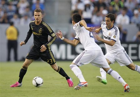 Los Angeles Galaxy's David Beckham (L) controls the ball as Real Madrid's Jose Maria Callejon (C) and Gonzalo Higuain (R) defend during the