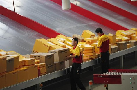 An employee carries a box at a workstation during an operational test of the new DHL North Asia Hub in Shanghai in this July 12, 2012 file p