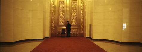 A security person closes a door as he guards an area of the Great Hall of the People, the venue of the 18th National Congress of the Communi
