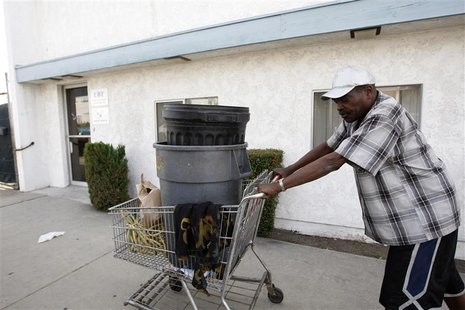 Carnell Weathersby pushes the cart he uses for collecting recyclables after picking up food from the Foothill Unity Center food bank in Monr