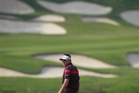Ian Poulter of England looks back on the 15th fairway during the final day of the WGC-HSBC Champions Tournament at Mission Hills in the sout