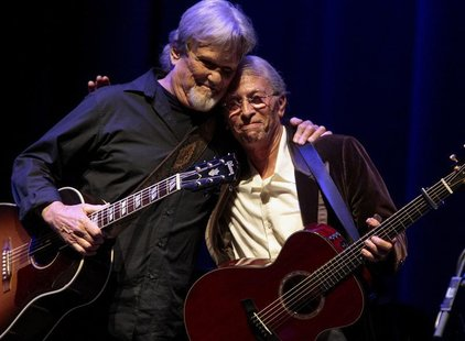 Kris Kristofferson (L) and Joel Rafael embraces each other after performing together during the Woody Guthrie Centennial Celebration Concert
