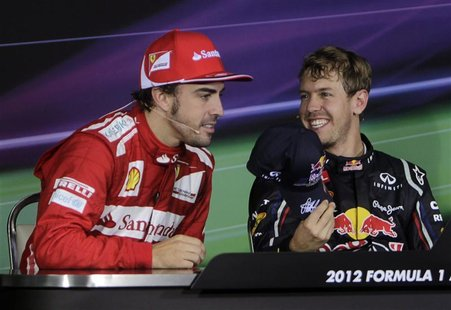 Red Bull Formula One driver Sebastian Vettel (R) of Germany offers his cap to Ferrari Formula One driver Fernando Alonso of Spain during a n
