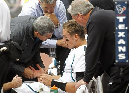 Jacksonville Jaguars quarterback Blaine Gabbert is examined on the bench after he was injured being sacked by Houston Texans safety Danieal