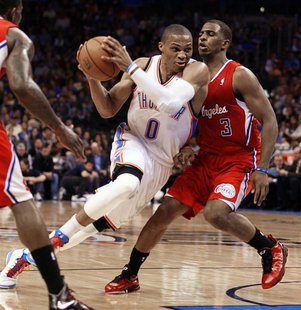 Oklahoma City Thunder guard Russell Westbrook passes Los Angeles Clippers guard Chris Paul (R) in the first half of their NBA basketball gam
