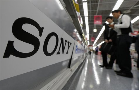 A Sony logo is seen as customers look at Sony digital cameras at an electronics shop in Tokyo, in this May 10, 2012 file photo. REUTERS/Kim