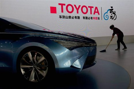 A worker cleans next to a Toyota NS4 plug-in hybrid concept car during the media preview of the 10th China International Automobile Exhibiti