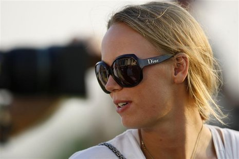 Denmark's professional tennis player Caroline Wozniacki looks on near the 18th green during the first round of the DP World Tour Championshi