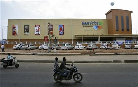 Two-wheelers move past the newly opened Bharti Wal-Mart Best Price Modern wholesale store in the southern Indian city of Hyderabad September