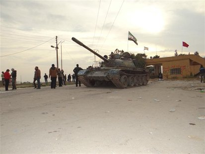 Residents and Free Syrian Army fighters pose near a tank after the fighters said they fought and defeated government troops from the town of