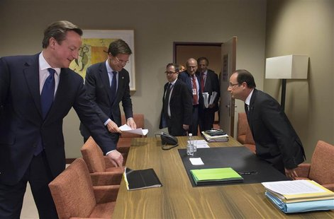 French President Francois Hollande (R) takes his seat before a meeting with British Prime Minister David Cameron (L) and Dutch Prime Ministe