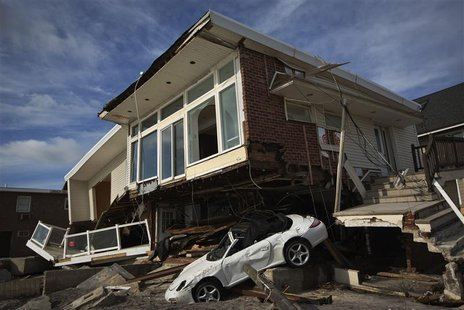 An automobile sits under a home damaged by superstorm Sandy in the Belle Harbor section of the Queens borough of New York November 14, 2012.