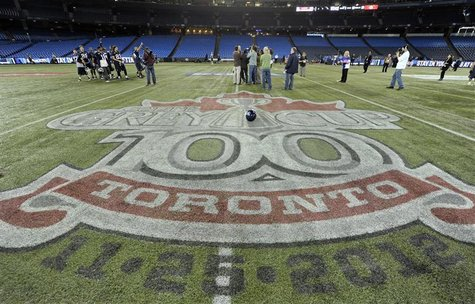 Toronto Argonauts players are interviewed on the field behind the Grey Cup logo during practice ahead of the 100th Grey Cup CFL football gam