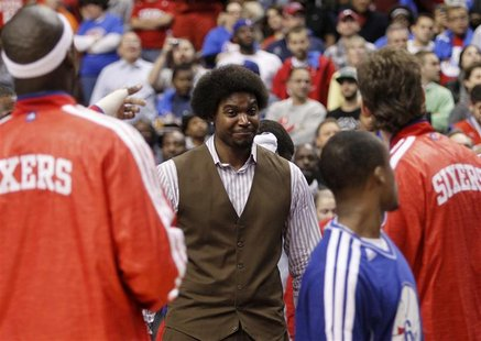 Injured Philadelphia 76ers center Andrew Bynum (C) smiles before the start of the NBA basketball game between the 76ers and the Denver Nugge