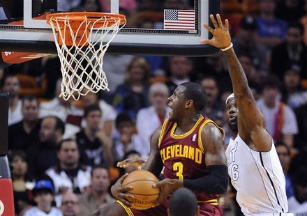 Miami Heat's LeBron James (R) defends Cleveland Cavaliers' Dion Waiters (L) during the first half of their NBA basketball game in Miami, Flo