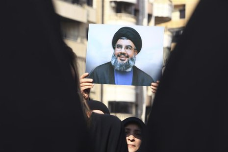 A Lebanese Hezbollah supporter carries a picture of Hezbollah leader Sayyed Hassan Nasrallah as she takes part in a ceremony marking Ashura