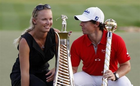 Rory McIlroy of Northern Ireland smiles at his girlfriend tennis player Caroline Wozniacki of Denmark as he poses with his trophy after the
