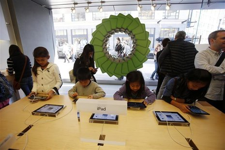 Young holiday shoppers interact with the iPad at the Apple Store during Black Friday in San Francisco, California, November 23, 2012. REUTER