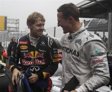 Mercedes Formula One driver Michael Schumacher of Germany (R) congratulates compatriot Red Bull driver Sebastian Vettel after the Brazilian