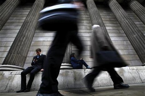 A man and woman use their mobile phones as commuters walk past the columns of the Bank of England in the City of London, July 3, 2012. REUTE