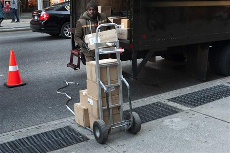 A UPS delivery man unloads boxes from a truck in New York November 26, 2012. Cyber Monday's online sales got off to a brisk start, sending e
