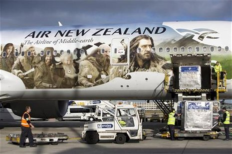 An Air New Zealand Boeing 777-300ER featuring livery advertising the film The Hobbit: An Unexpected Journey is loaded by ground crew after l