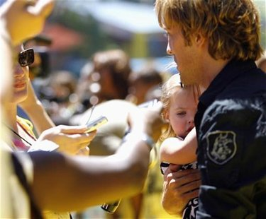 Larry Birkhead, ex-boyfriend of the late Anna Nicole Smith, holds his daughter Dannielynn as he is being interviewed at the opening of The S