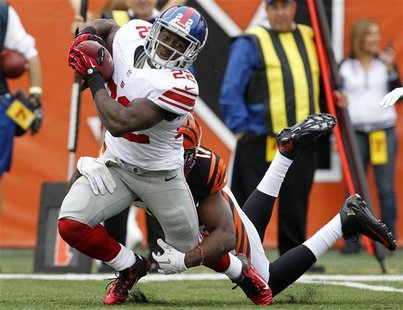 New York Giants' David Wilson (22) is tackled by Cincinnati Bengals' Mohamed Sanu (12) during the first half of play in their NFL football g