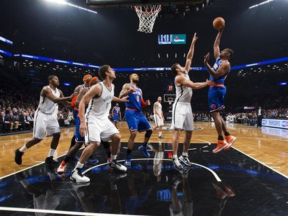 New York Knicks forward Kurt Thomas (R) shoots over Brooklyn Nets forward Kris Humphries (2nd R) in the second quarter of their NBA basketba