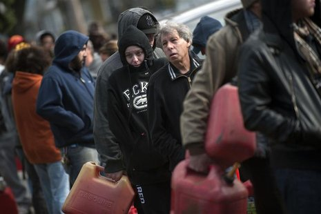 Residents try to keep warm as they line up for gasoline at a temporary fueling station at the National Guard armory in the Staten Island Bor