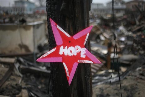 "A wooden star with the word ""Hope"", is left in front of a burnt house in Breezy Point, almost a month after the neighborhood was left devast"
