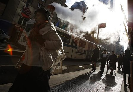 Pedestrians walk along Lexington Avenue past a steam vent in New York, November 28, 2012. REUTERS/Carlo Allegri