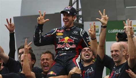 Red Bull Formula One driver Sebastian Vettel of Germany (C) celebrates winning the world championship with Team Principal Chrisian Horner (L