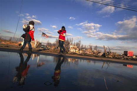 Red Cross volunteers walk past the remaining foundations of homes destroyed by the storm surge of superstorm Sandy in the Staten Island boro
